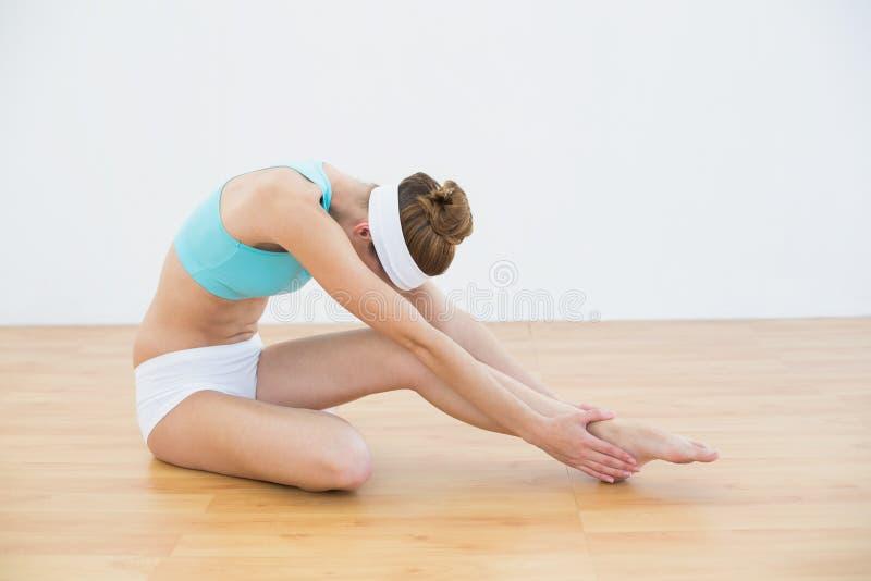 Abiti sportivi d'uso della bella donna snella che allungano la sua gamba fotografia stock