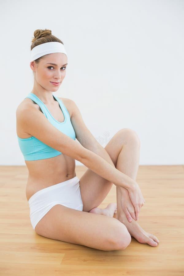Abiti sportivi d'uso della bella donna snella che posano seduta sul pavimento immagine stock libera da diritti