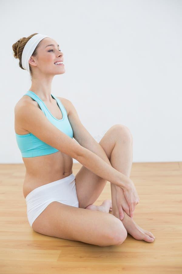 Abiti sportivi d'uso della donna abbastanza sportiva che si siedono sul pavimento fotografia stock