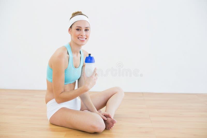 Abiti sportivi d'uso della donna esile attraente che si siedono sul pavimento immagini stock libere da diritti