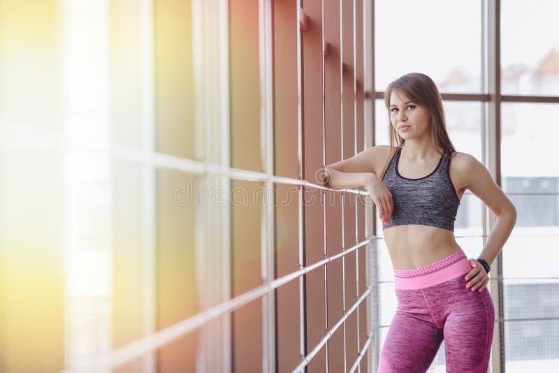 Abiti sportivi d'uso della ragazza in una palestra vicino alla finestra fotografia stock libera da diritti
