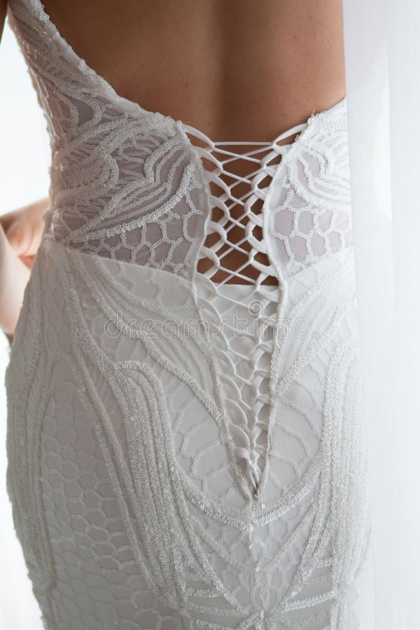Abito di nozze che è legato al grande primo piano posteriore del dettaglio Giovane biondo in vestito da cerimonia nuziale Vista p immagine stock