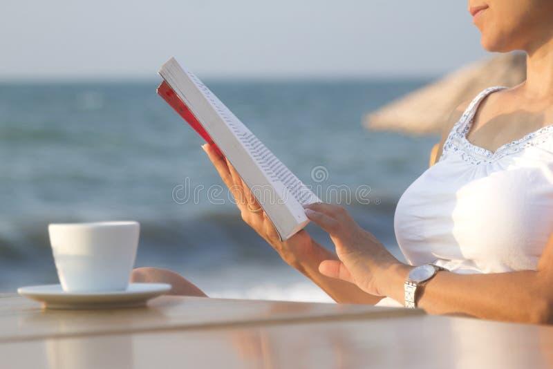 Ablesen eines Buches an der Küste stockbild
