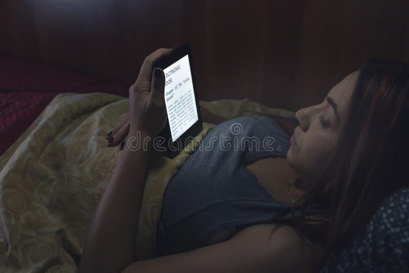 Ablesen eines ebook im Bett stockfotografie