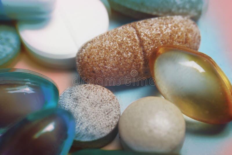 Ablets和胶囊,健康宏指令 各种各样的药片堆在颜色背景的 LSD药片药物,明亮的荧光的药片 免版税库存图片