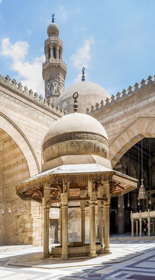Ablution fountain at historic Sultan Barquq Mosque with dome and minaret in background, Cairo, Egypt. Ablution fountain mediating the courtyard of public stock image