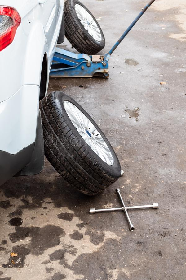 Abmontierte Räder nahe angehobenem Fahrzeug draußen stockfotografie