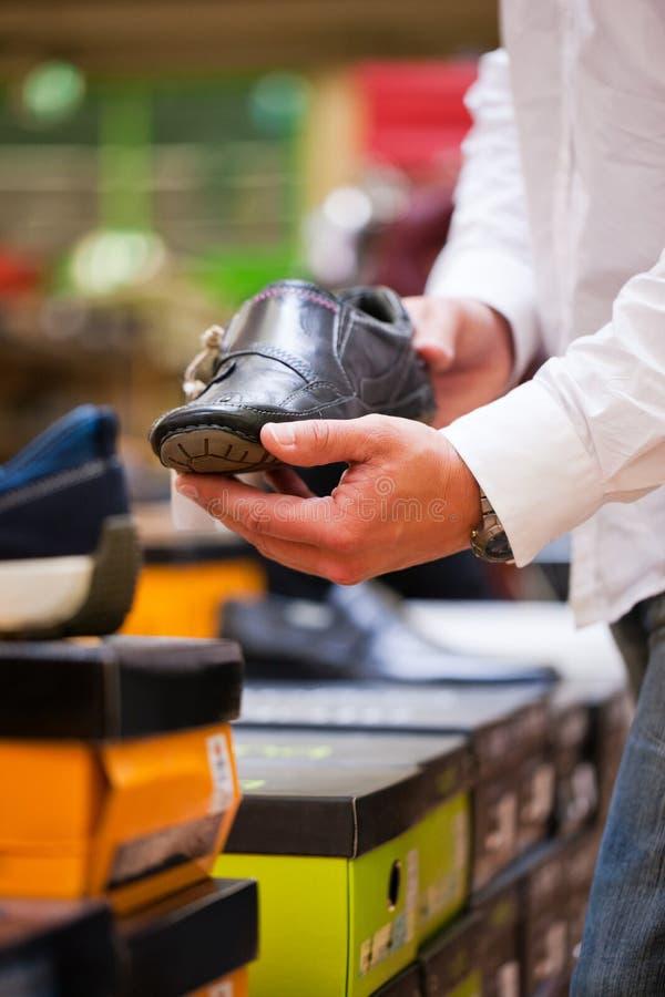 Abnehmer, der stilvollen Schuh am Supermarkt anhält lizenzfreie stockfotografie