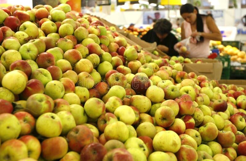 Abnehmer, die für Äpfel am Supermarkt kaufen lizenzfreie stockbilder