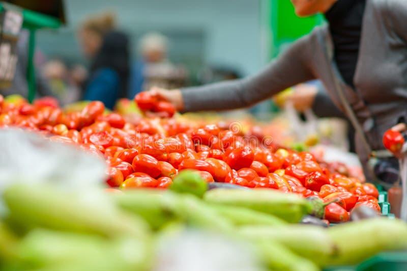 Abnehmer, die Tomaten im Supermarkt auswählen stockfoto