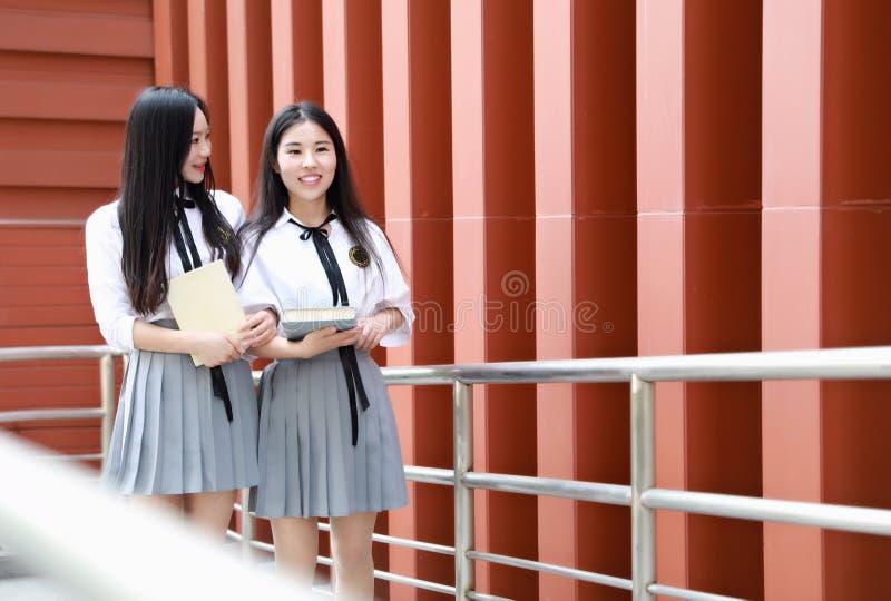 Abnutzungs-Studentenanzug mit zwei lächeln reizender asiatischer chinesischer hübscher Mädchen in den Schulbesten Freunden Lachen stockbild