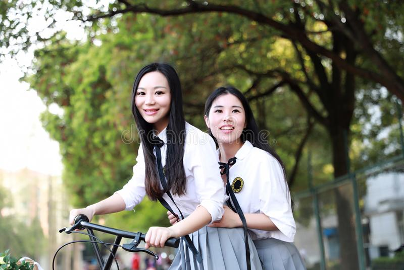 Abnutzungs-Studentenanzug mit zwei lächeln reizender asiatischer chinesischer hübscher Mädchen in den Schulbesten Freunden Lachen lizenzfreie stockbilder