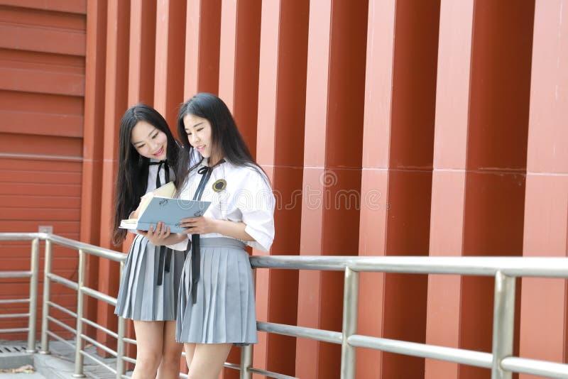 Abnutzungs-Studentenanzug mit zwei lächeln reizender asiatischer chinesischer hübscher Mädchen in den Schulbesten Freunden Lachen stockfotos