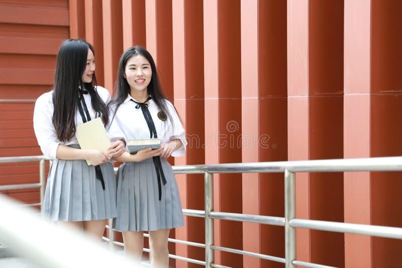 Abnutzungs-Studentenanzug mit zwei lächeln reizender asiatischer chinesischer hübscher Mädchen in den Schulbesten Freunden Lachen stockfotografie