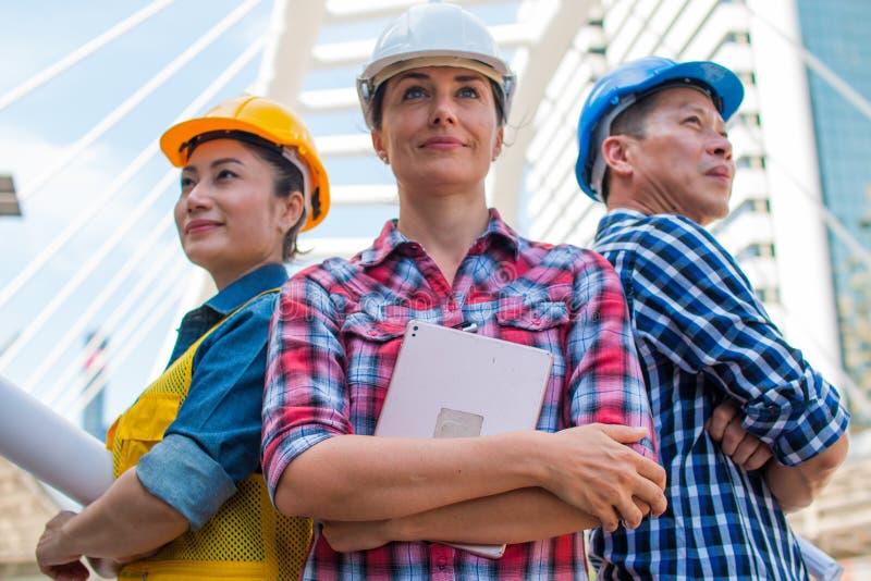 Abnutzungsschutzhelm-Technikstellung mit drei Wirtschaftsingenieuren mit den Armen kreuzte auf Gebäude draußen lizenzfreie stockbilder