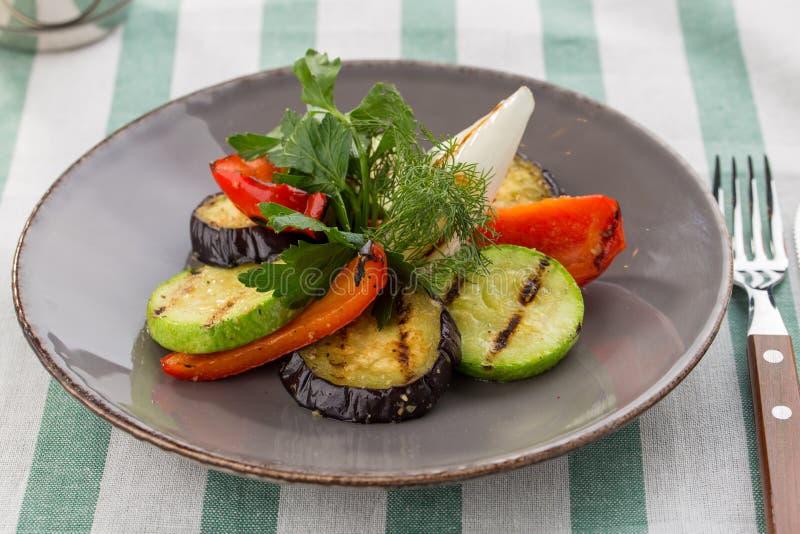Abobrinha grelhado dos vegetais, pimenta de sino e aneto e salsa frescos na placa no fundo de matéria têxtil foto de stock royalty free