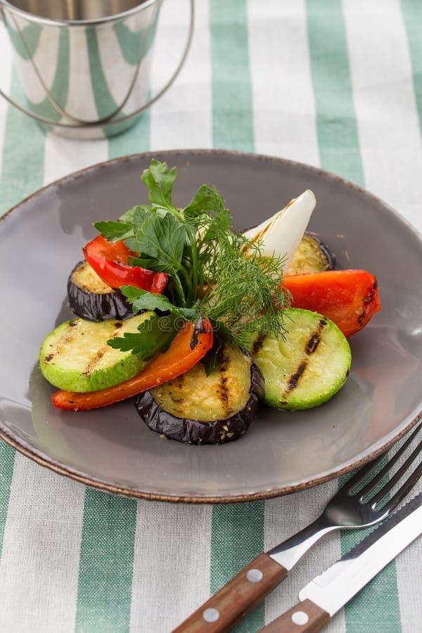Abobrinha grelhado dos vegetais, pimenta de sino e aneto e salsa frescos na placa no fundo de matéria têxtil imagens de stock royalty free