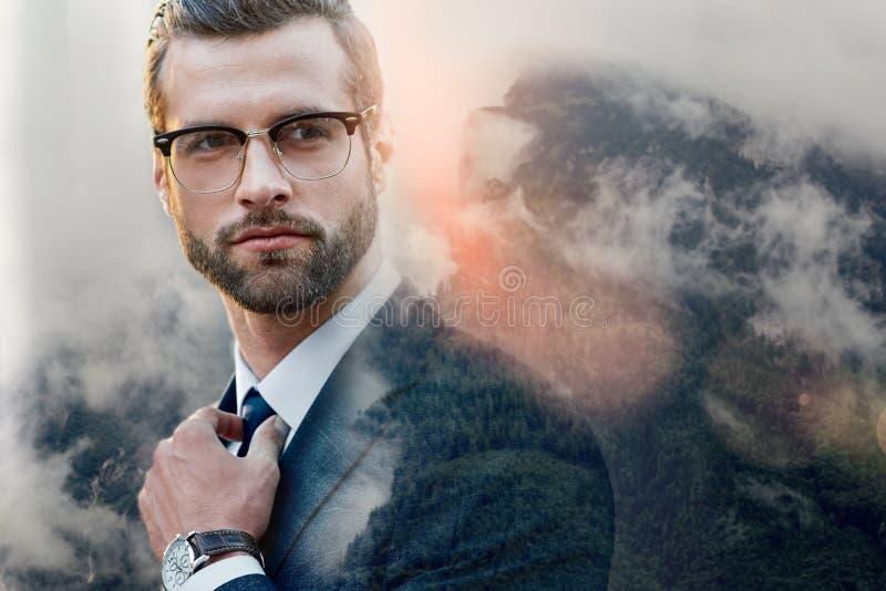 Abogado acertado Hombre de negocios confiado en los vidrios que ajustan su corbata mientras que se coloca al aire libre con la na imagen de archivo