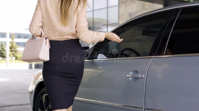 Abogado de sexo femenino acertado que gira la alarma para coches y que camina al edificio de oficinas imagen de archivo