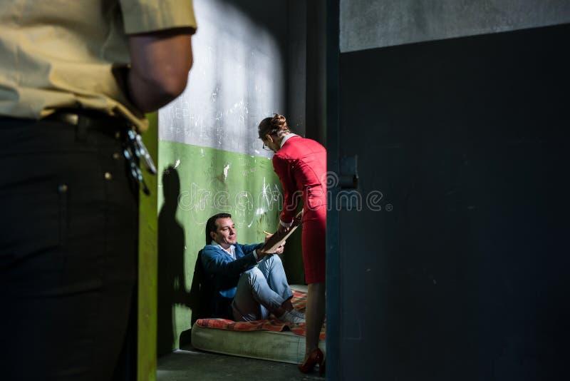 Abogado de sexo femenino dedicado que visita a un interno joven en una celda de prisión obsoleta fotografía de archivo libre de regalías