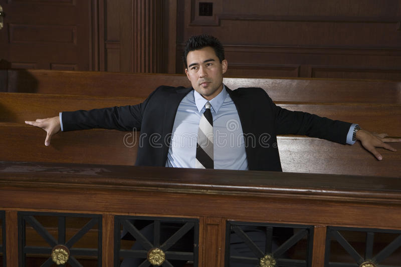 Abogado de sexo masculino pensativo Sitting In Courtroom imagen de archivo