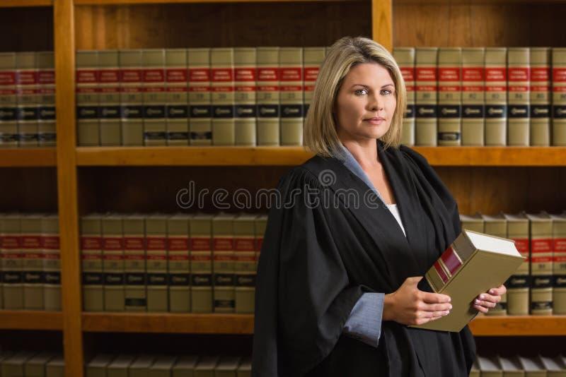 Abogado que sostiene el libro en la biblioteca jurídica imagen de archivo