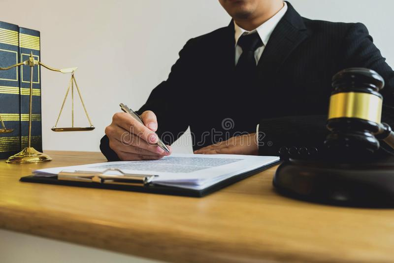 Abogado que trabaja con los papeles del contrato en la tabla en oficina abogado del consultor, abogado, juez de la corte, concept foto de archivo