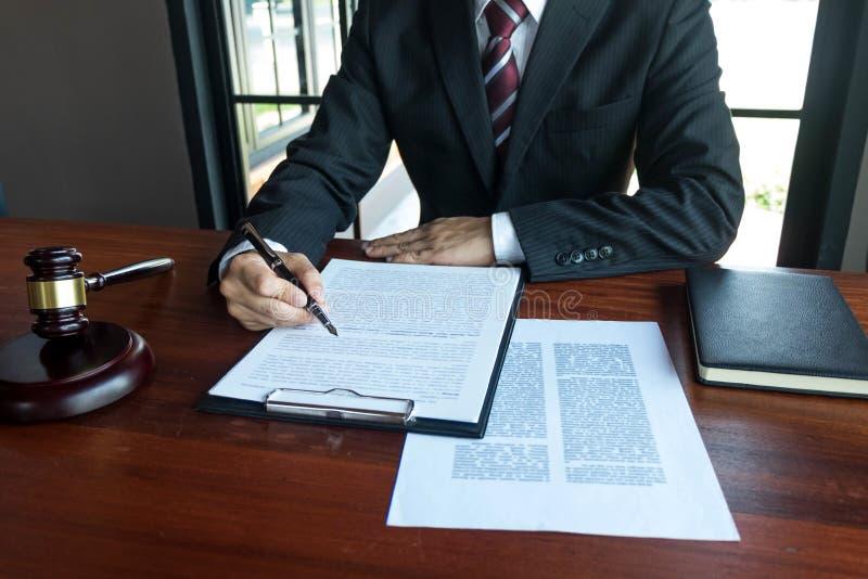 Abogado que trabaja con los papeles del contrato en la tabla en oficina abogado del consultor, abogado, juez de la corte, concept fotografía de archivo