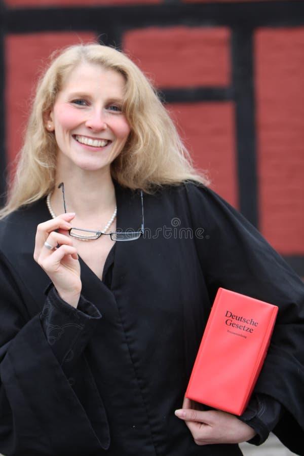 Abogado sonriente cómodo con el libro de ley rojo bajo h fotografía de archivo