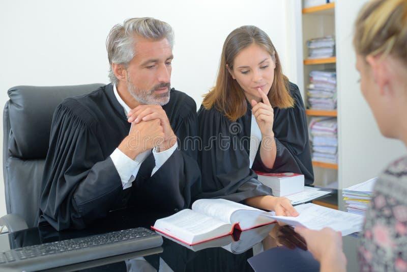 2 abogados con el cliente femenino en oficina fotos de archivo
