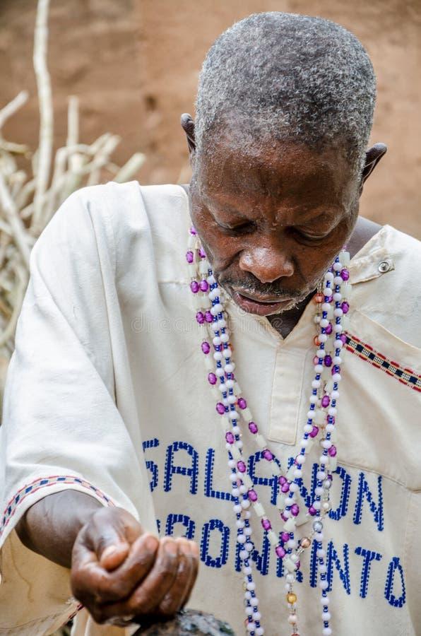 Abomey Benin - mars 07, 2014: Afrikansk voodoopräst som ser ner koncentrerat, medan utföra religiös ritual royaltyfri foto