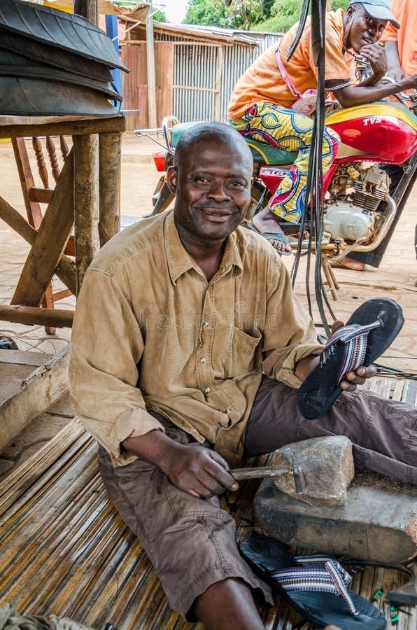 Abomey Benin, Marzec, - 07, 2014: Uśmiechnięty Afrykański mężczyzna obsiadanie na ziemi i produkcja męczymy trzepnięcie klapy w u fotografia stock