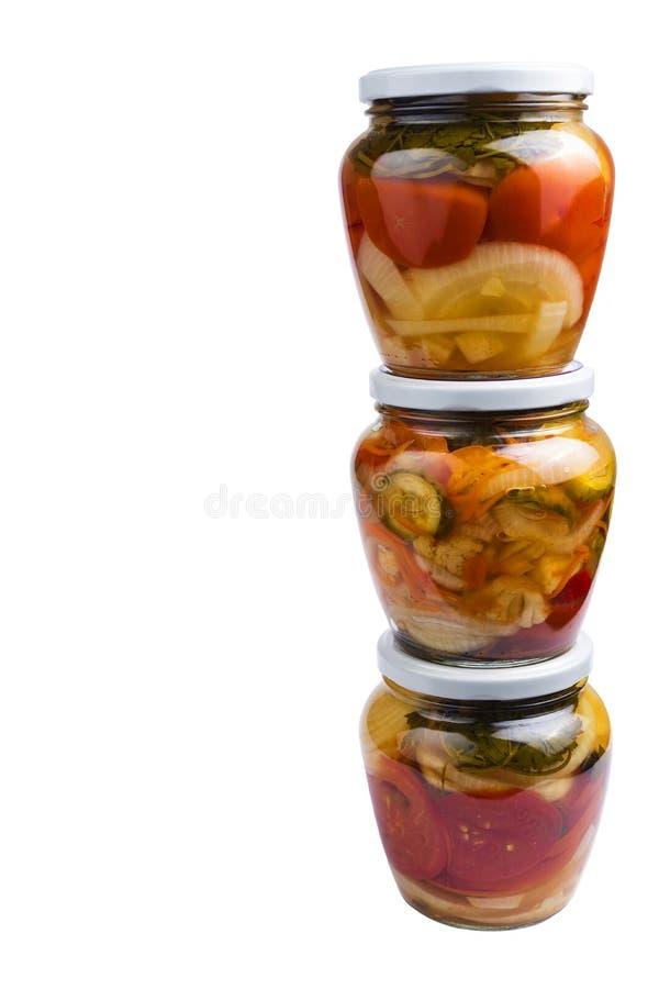 Abondance de beaux pots en verre avec des salades faites maison végétales d'isolement sur le fond blanc images stock