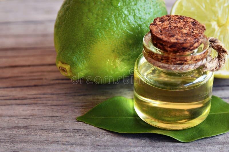 Abone el aceite con cal esencial en una botella de cristal con las frutas frescas de la cal Concepto del balneario, del aromather foto de archivo libre de regalías