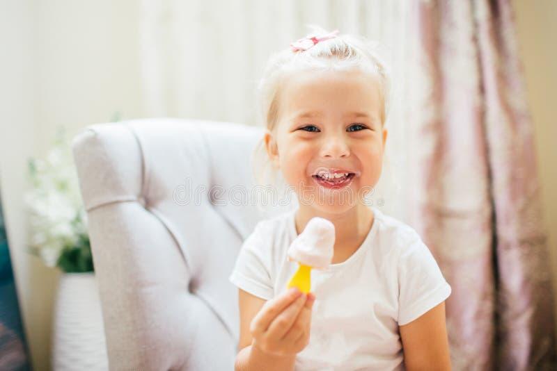 Aborable som ler blonda 3 år, behandla som ett barn flickan som äter hemlagad glass och att skratta royaltyfria bilder