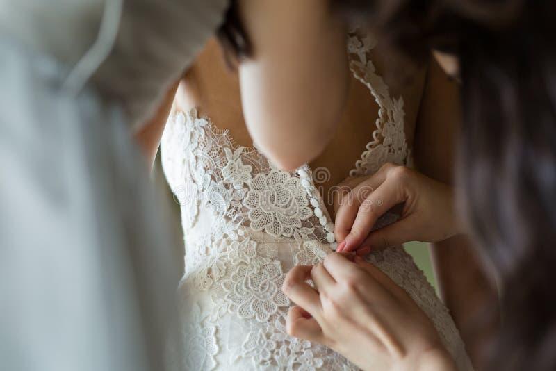 Abotoando o vestido de casamento fotos de stock