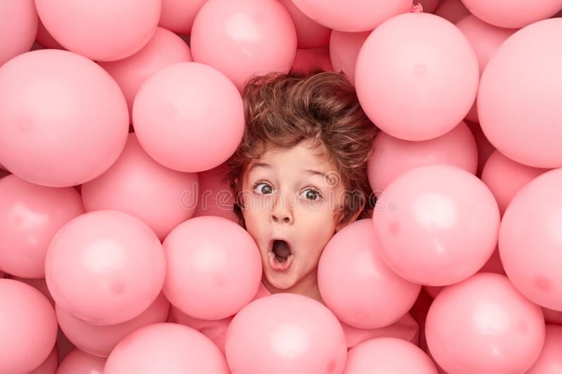 Funny boy under pink balloons. From above astonished little boy looking away while having fun under heap of pink balloons during party royalty free stock images