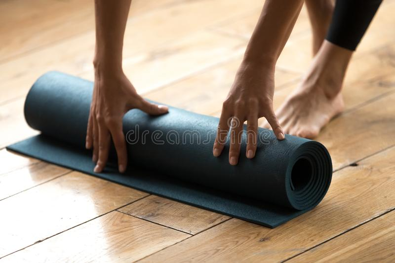 Woman beginning her practice and unrolling blue fitness exercise stock photos