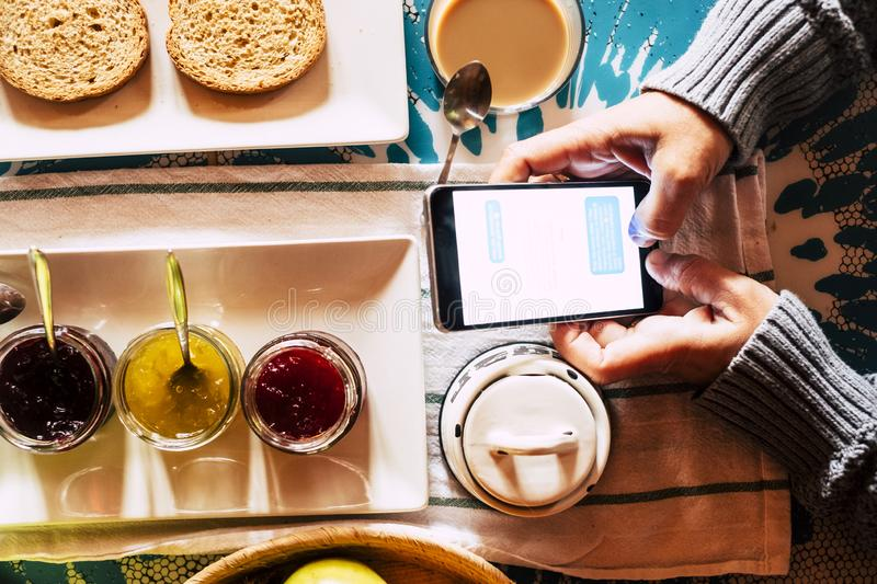 Above close up view of people doing healthy breakfast while answer messages on mobile phone -chat activity on device at home or royalty free stock images