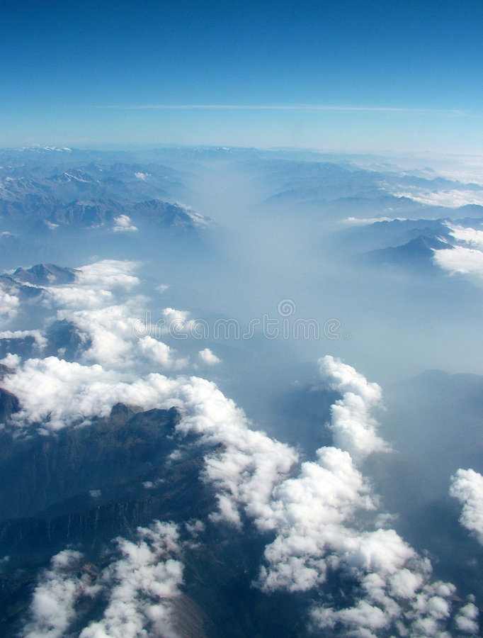 Above the clouds. A view of the earth above the clouds from an airplane royalty free stock image