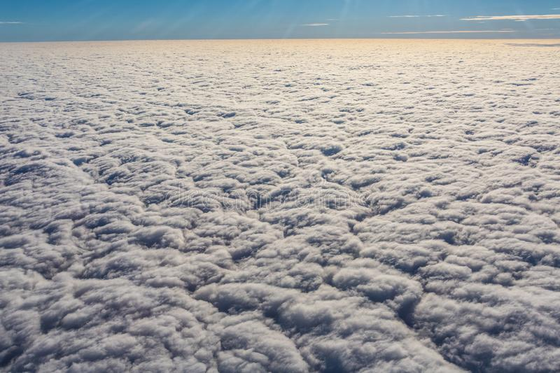 Above the clouds - endless view of clouds covering the earth. Looking down the clouds royalty free stock image