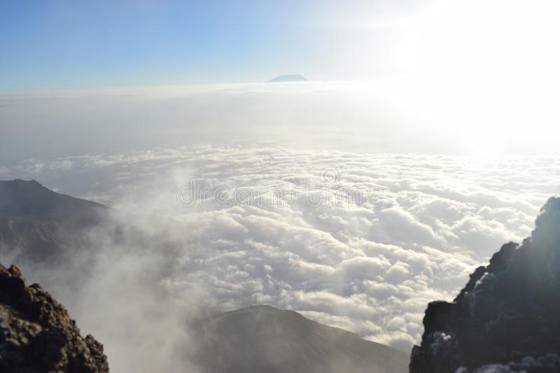 Above the clouds at Mount Meru. With Mount Kilimanjaro at the background. Arusha national park, Tanzania stock photos