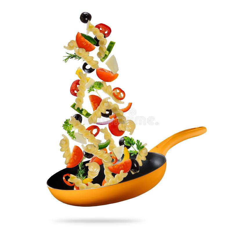 Flying food. Concept of flying food preparation of pasta and vegetable in pan stock image