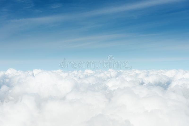 Above the cumuls clouds, blue sky background. High up, above the cumulus clouds, blue sky background stock image