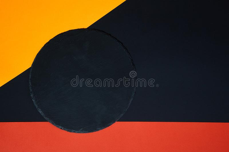 From above of empty black slate serving board on multicolored background with geometric composition.  stock photography