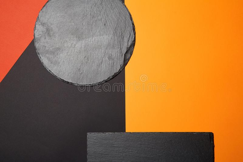From above of empty black slate serving board on multicolored background with geometric composition.  royalty free stock image