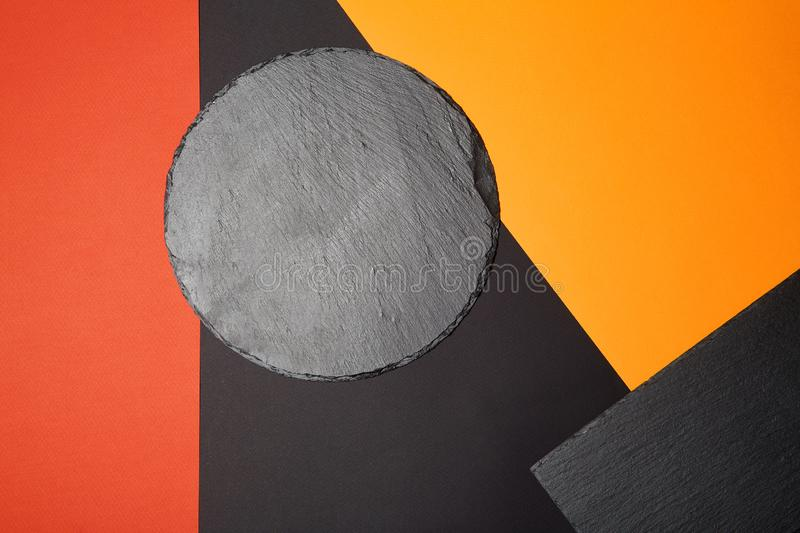 From above of empty black slate serving board on multicolored background with geometric composition.  royalty free stock photos