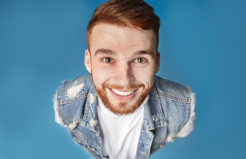 Above portrait of funny millennial redhaired guy, smiling upwards at camera stock images