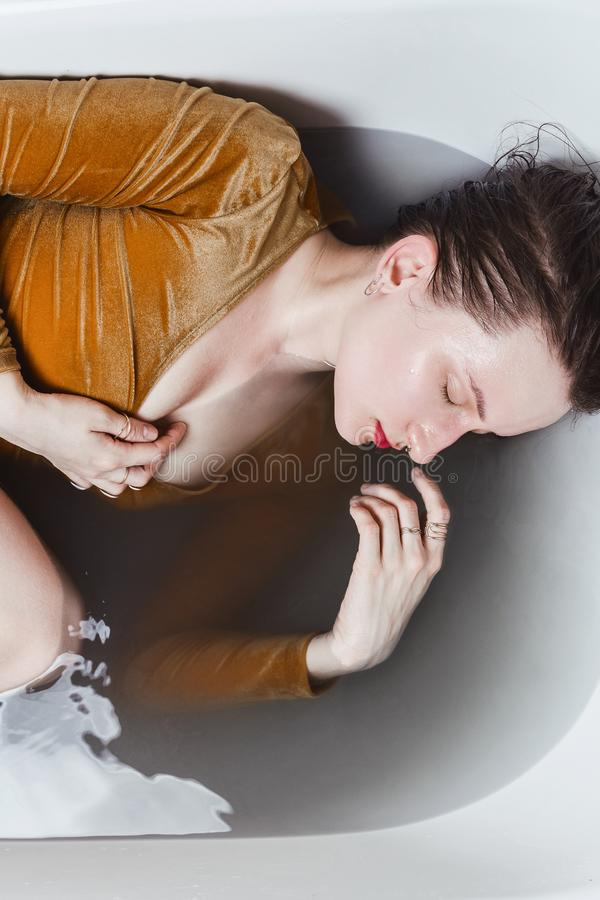 Portrait of young adult woman lying in bathtub filled with charcoal water royalty free stock image