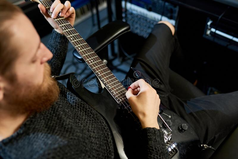 Crop musician playing guitar in studio stock photography